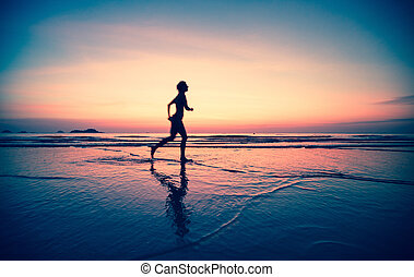 Blured silhouette of a woman jogger on the beach at sunset, picture-in-surreal colours.