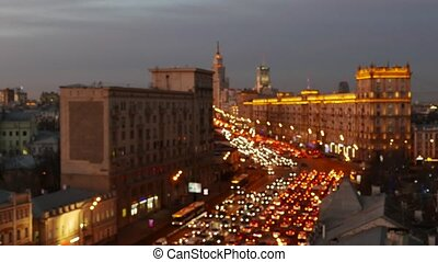 Blured view to motion cars traffic with lights on highway and lighted buildings in Moscow
