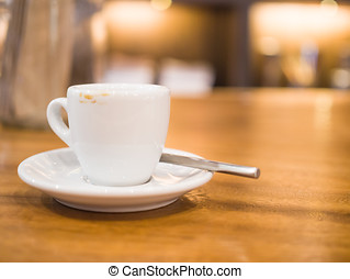 Blurred a cup of coffee on wooden table and Coffee shop background