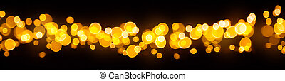 Blurred abstract golden spot lights on black background