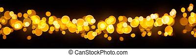 Blurred abstract golden spot lights on black background -...