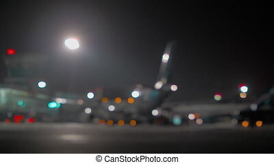 Wide blurred shot of a jet airplane standing near the airport terminal at night