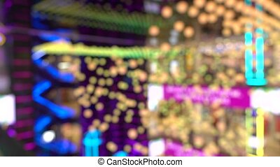 Blurred atrium of a modern shopping mall with bright LED lights. 4K bokeh footage