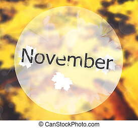 """Blurred autumn leaves background with text """"November"""""""