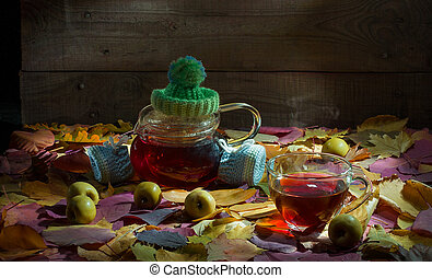 Blurred autumn tree background with hot steaming cup of tea