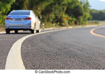 Blurred back side of new silver car parking on the asphalt road, Focus on road