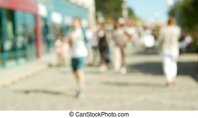 Blurred background. Abstract people walking along the promenade of the city