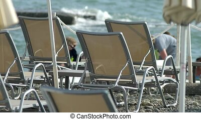 Blurred background. beach chairs and umbrellas on the beach, unrecognizable people resting.