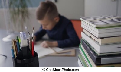 Blurred background boy who does homework. On the table there are books, notebooks and pencils. School education equipment tools