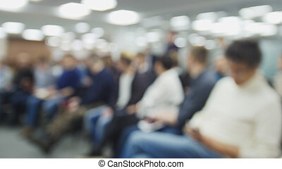 Blurred background - business meeting - a lot of people sitting at a seminar or lectures - horizontal