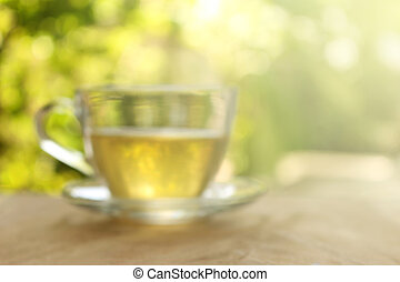 Blurred background : Cup of tea on a blurred background of nature with burst light