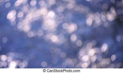Blurred background flowing river top view. Nature backdrop, natural background. Motion blurred background of purple color with white glittering bokeh spots. Rotating abstract background. Seamless loop