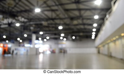 Abstract blurred background. Inside big building. People walk inside space. Lots of glowing spotlights, lamps shine indoors. Beige floor, black-gray ceiling. Many stands and equipment for exhibitions
