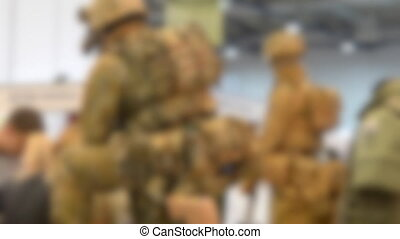 Blurred background. Mannequin dressed various body armor and protective helmets. Example military uniform outfit.