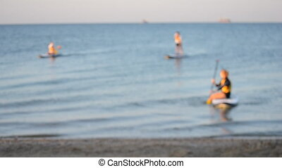 Blurred background. Many people standing and sitting swim on sup boards, floating board of sea water surface near sandy shore on summer day. Travel, tourism, holiday, vacation, trip, nature, natural
