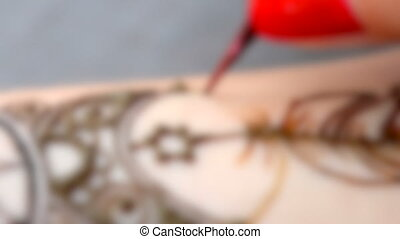 Blurred background. HD 1080 Master put a temporary henna tattoo in the form leaf closeup