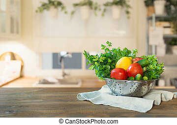 Blurred background. Modern kitchen with fresh vegetables on wooden tabletop, space for you and display products.