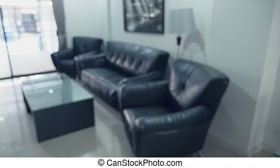 blurred background. modern living room interior with black leather furniture and glass table