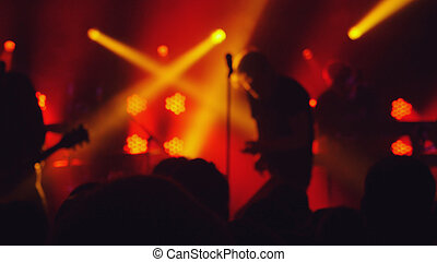 Blurred background of people crowd partying at rock concert in a night club.