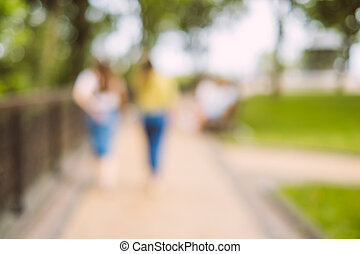 Blurred background of people walking in the park