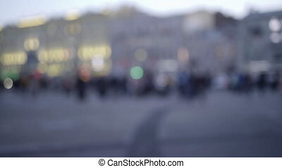 blurred background of people walking in the street or square during evening rush hour