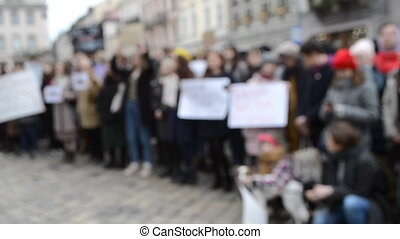 Blurred background. People are standing in square on rally protest demonstration. Many protesters stand on street in strike with banner posters in hands. Crowd people in background on street.