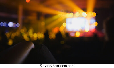 Blurred background - the crowd of silhouette of people dancing at the concert
