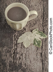 blurred background with cup of coffee autumn leaves on table