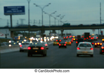 Blurred background with lights of cars at dusk
