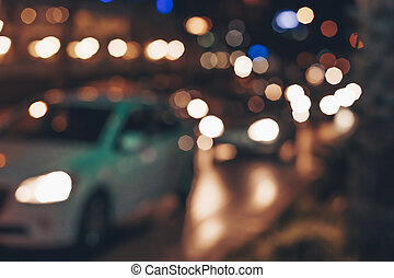 Blurred background with lights of cars in traffic jam. Abstract background with cars on night street.