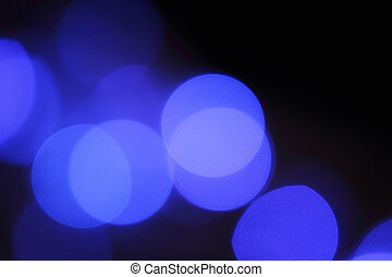 Blurred background with round shaped lights on black -...