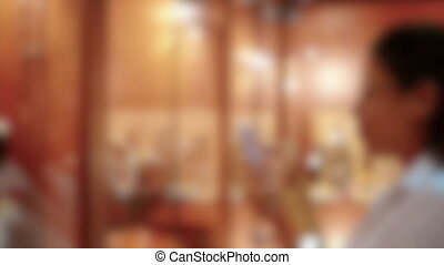 Blurred background. Young girl smiling, standing near the windows in the store and photographs phone
