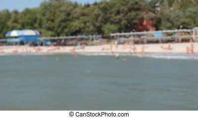 Blurred beach view from the sea. No focus