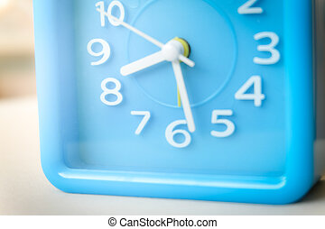 Blurred blue clock in over white background.