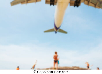 Blurred blue sea and white sand beach with some people and plane