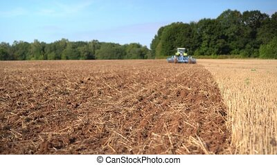 Blurred blue tractor discing stubble field soil with special...