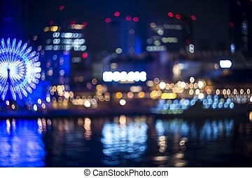 Blurred bokeh night harbor lights background with ferris wheel