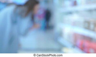 Blurred bokeh shot of young woman choosing perfume in a...