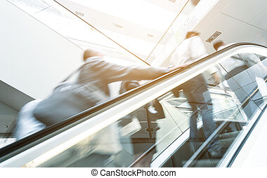 Blurred business people at a escalator