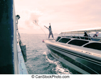 Blurred captain man cast rope on boat