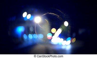 Blurred car lights in the night handheld shot. Flares of vintage lens.