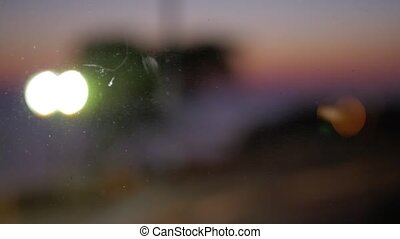 Blurred cars driving with headlights on. Evening view through the glass