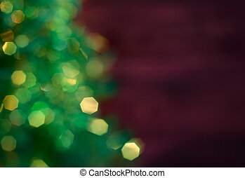 Blurred Christmas tree with garland, green bokeh on a dark red background blurred