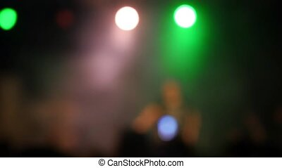 Blurred crowd at concert in front of bright colorful stage lights in slow motion. 1920x1080