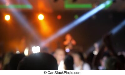 Blurred crowd have fun on concert and bright colorful stage lights. Slow motion. 1920x1080