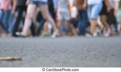 Blurred crowd of people walking in downtown. Unrecognizable pedestrians crossing crosswalk in the city. Urban lifestyle. Low angle view