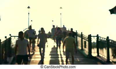 Blurred crowd on sunny park arched bridge. Super slow motion shot, warm evening colors