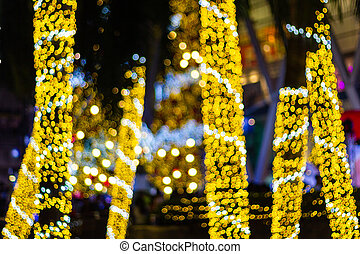 Blurred Decorative outdoor string lights hanging on tree in the garden at night time