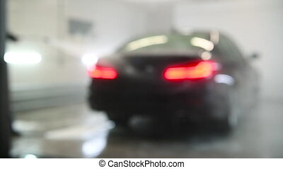 Blurred defocused footage of washing with a high pressure sprayer at car care center for background