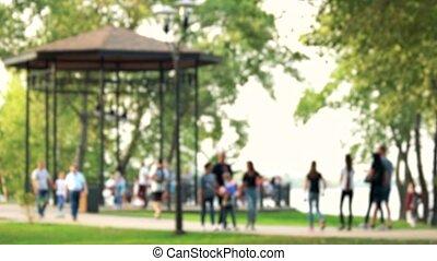 Blurred defocused people are walking in the park.